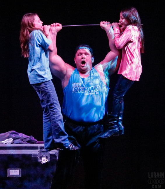 The Strongman lifted these girls over his head and spun them in a circle before putting them down.