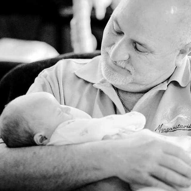 Black and white photo of a grandfather holding his newborn grandson for the first time.