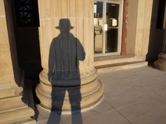 Photo of a person's shadow on the column of an old bank building.