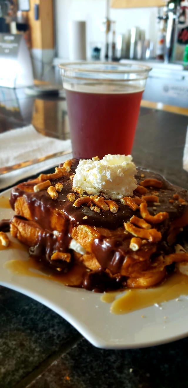 French toast covered in chocolate, broken pretzel pieces, and whipped cream. Served with a beer from Bascule Brewery.