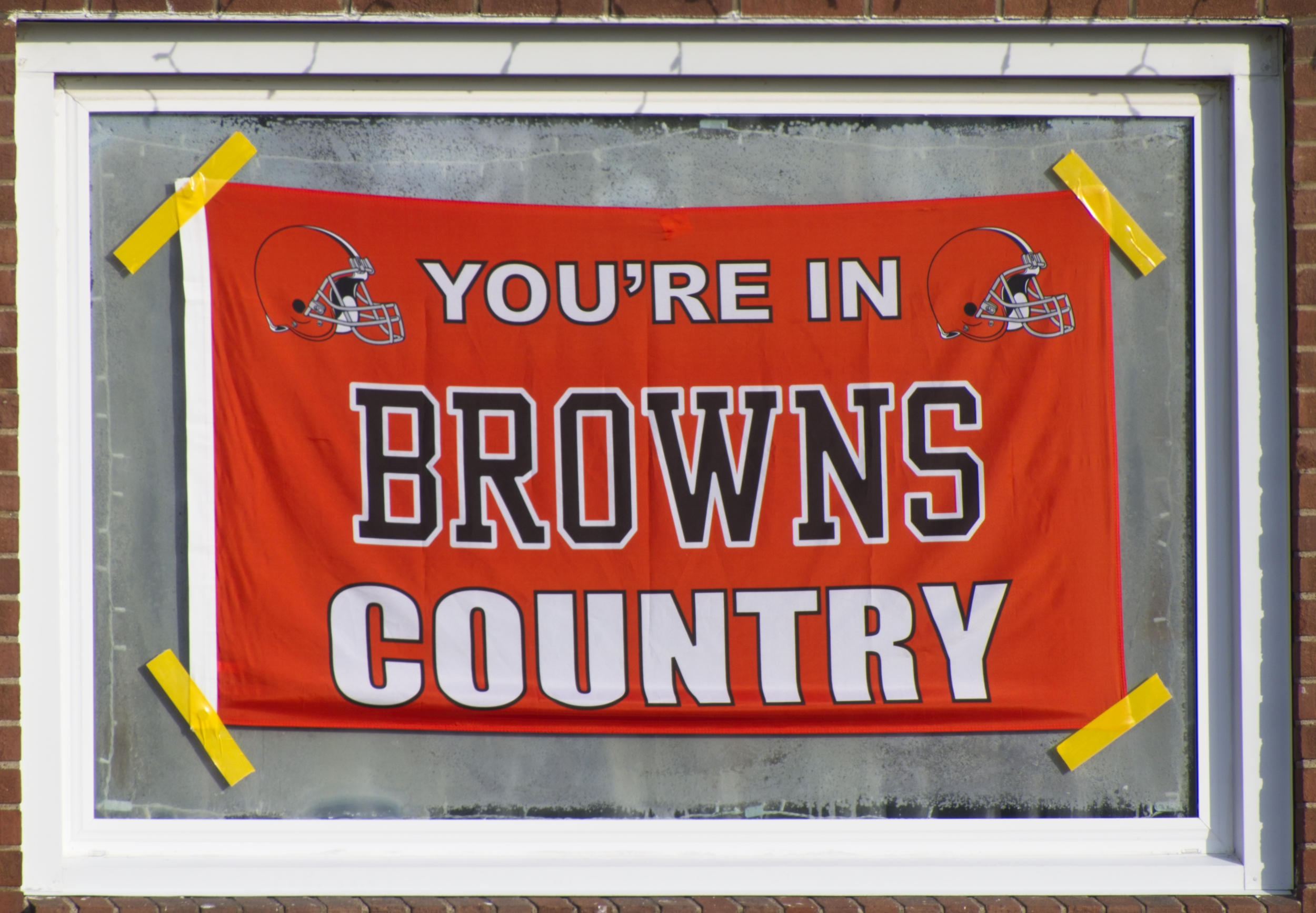 """Orange flag reading """"You're in Browns Country"""" taped to front window of a residence in South Lorain, OH"""