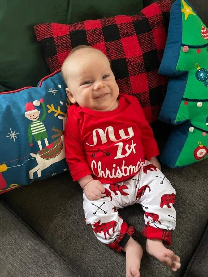 Smiling infant dressed in My First Christmas pajamas and propped against festive pillows