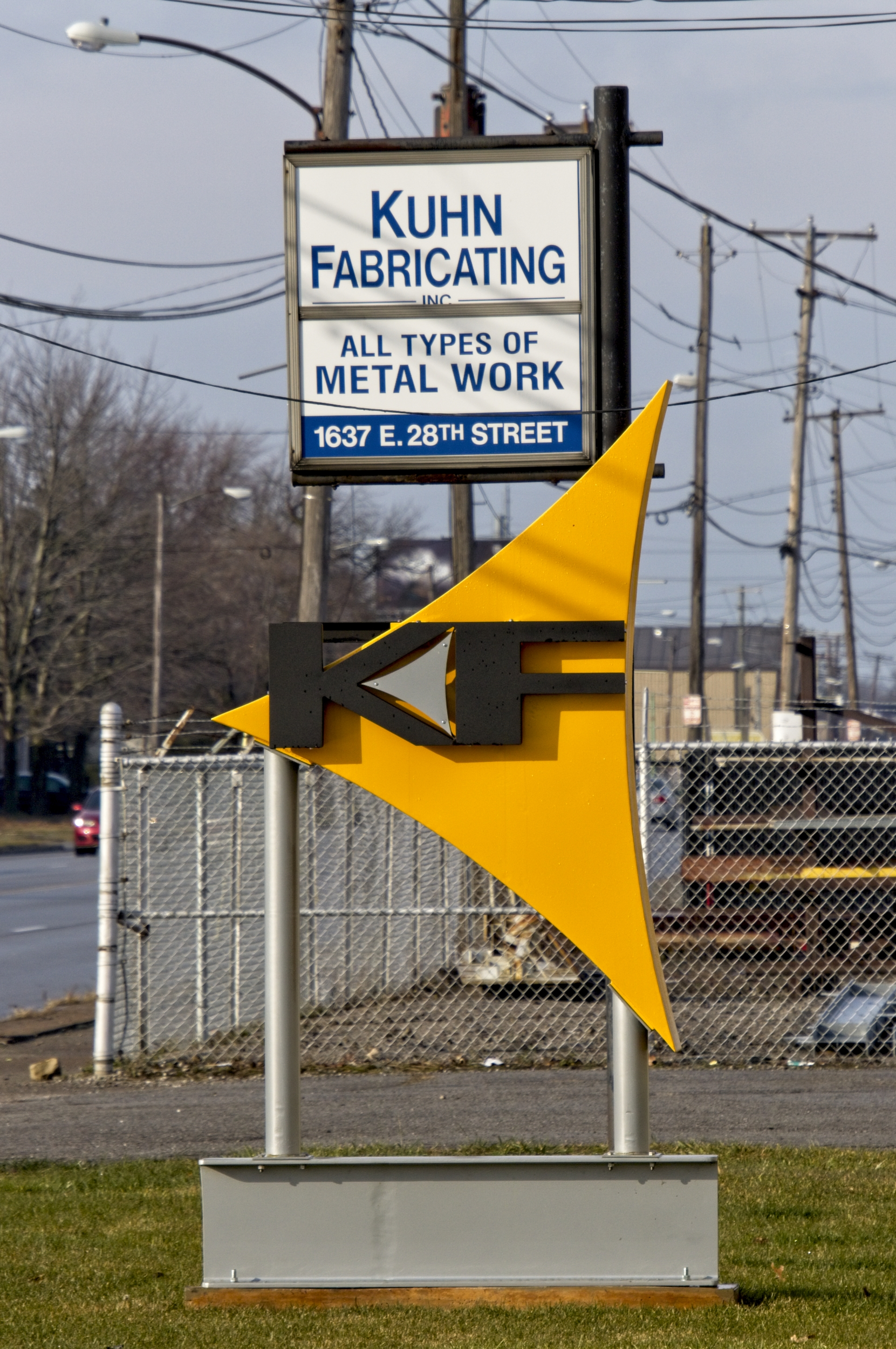 2 signs for a business. One is square and has the name of the business, what they do, and the address in blue letters on a white background. The other sign is the company logo: the letters K and F in black with a small gray triangular accent between them, all on a yellow triangular background. This is mounted to two metal posts which are mounted to the top of a section of steel beam.