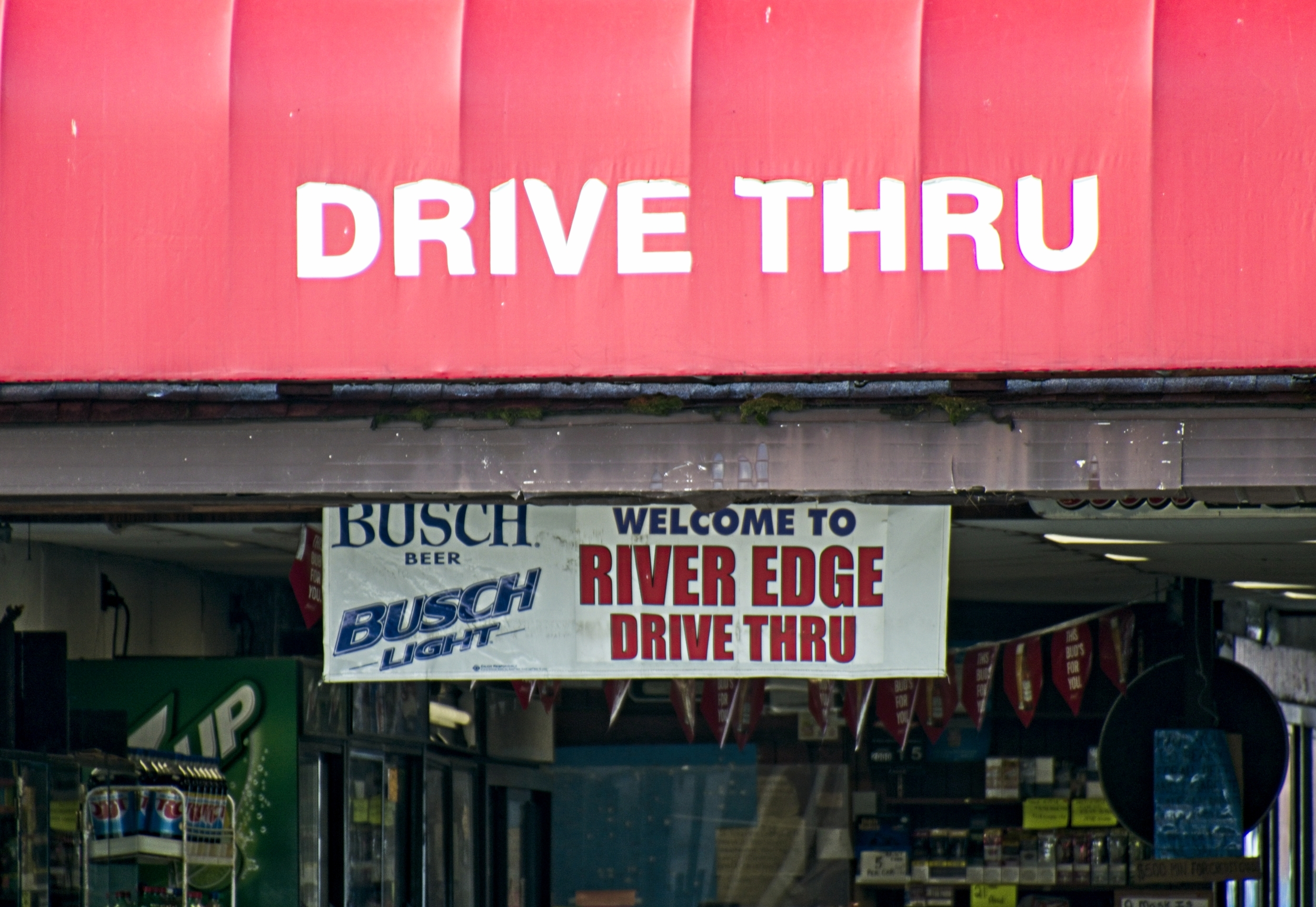 "Red awning marked ""Drive Thru"" over entrance, banner sign inside welcoming patrons."