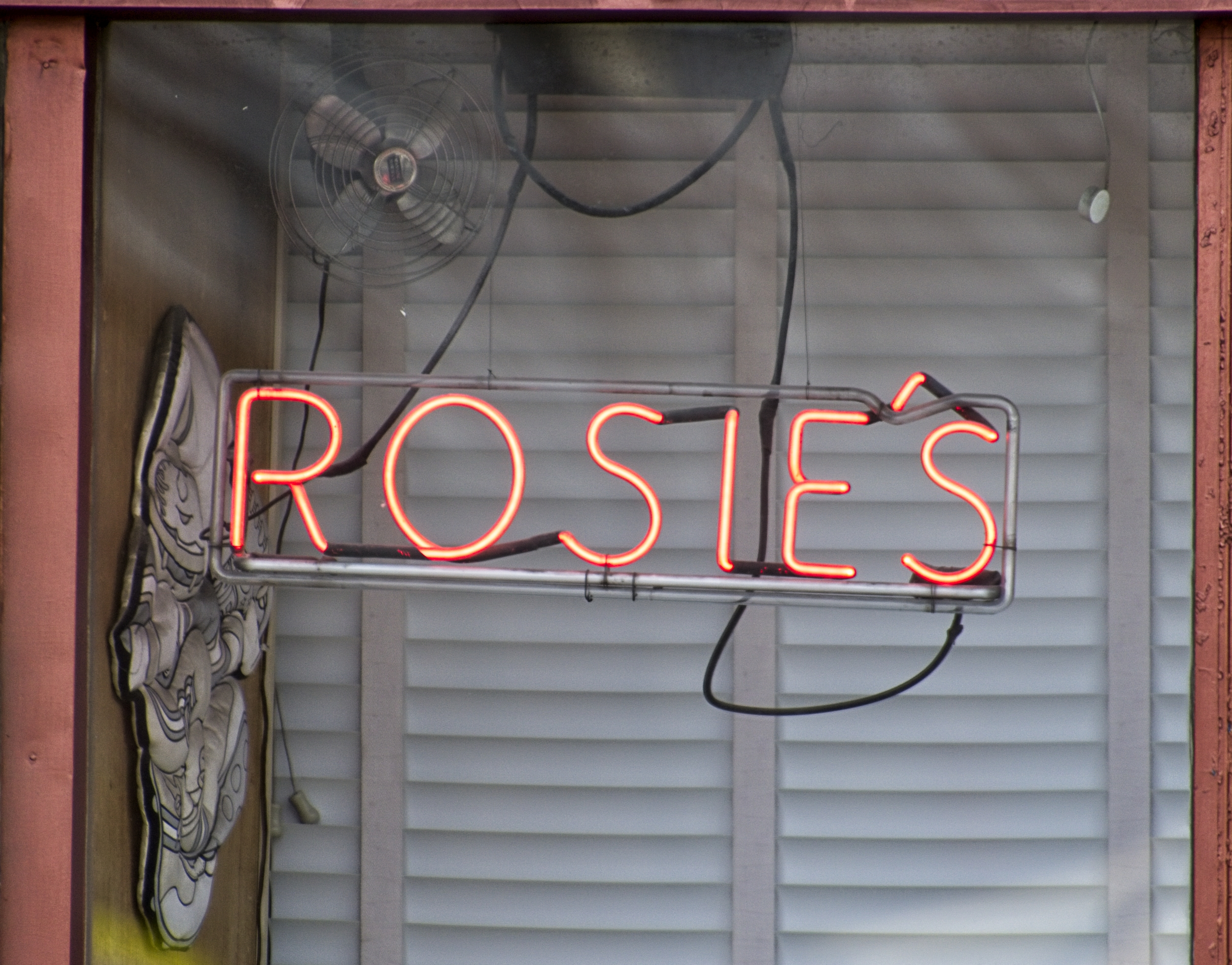"Neon sign reading ""Rosie's"" in the window of Rosie's Pizza in Lorain, OH"