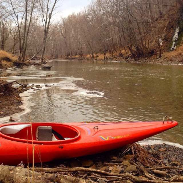Red kayak sitting on the riverbank. The water is muddy brown, the trees are bare, and there is some ice along the shoreline.