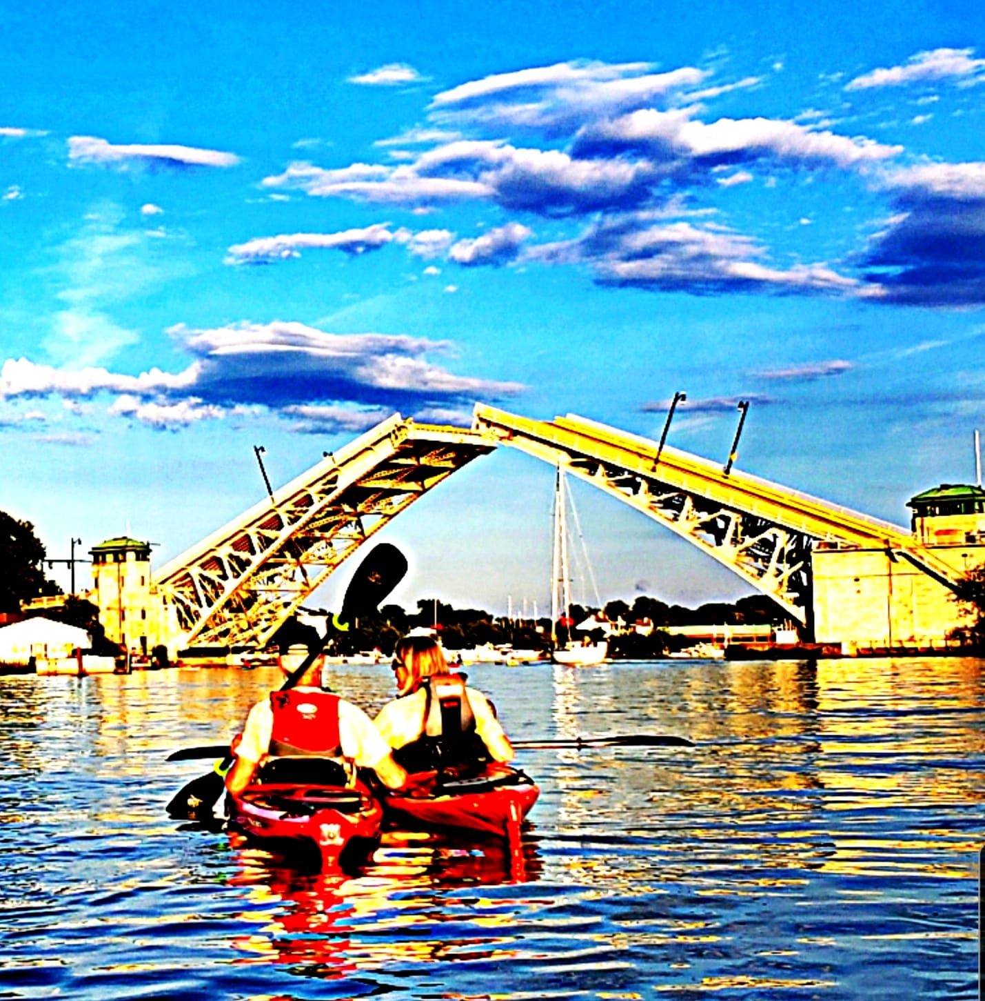Heavily edited image of 2 kayakers in the river in front of a partially open drawbridge