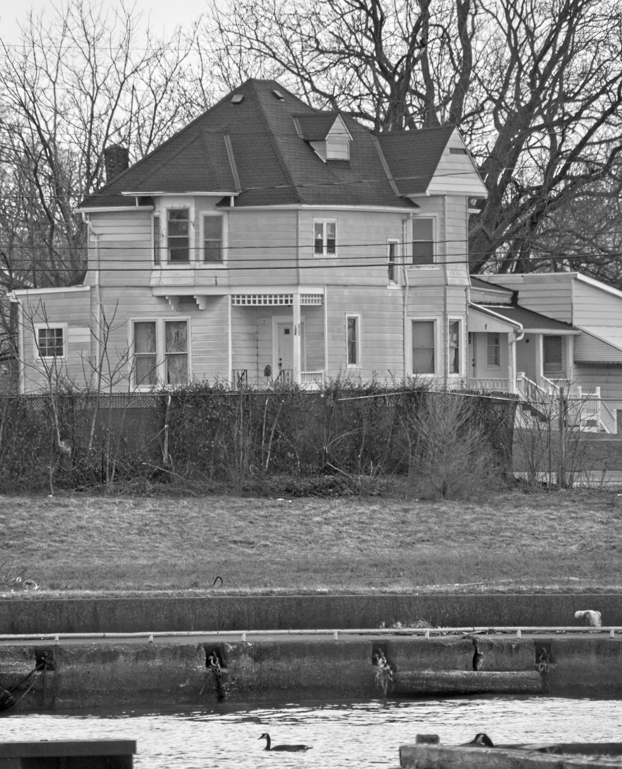Black and white photo of the oldest house in Lorain overlooking the Black River. Pier and river in the foreground.