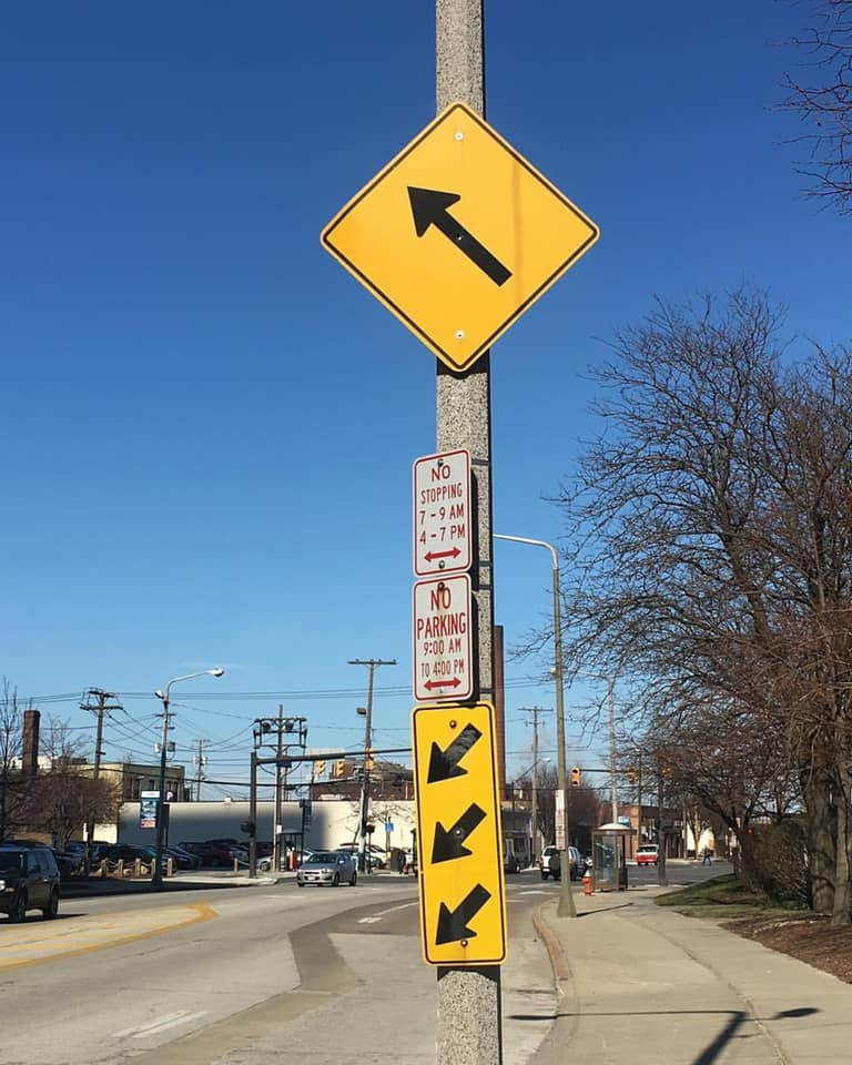 Road signs on a post. One sign is 3 arrows pointing down and another sign is one large arrow pointing up at an angle.