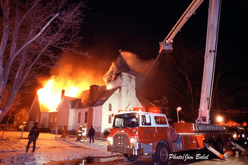 Large old church on fire in the background, large fire truck with aerial ladder extended in foreground
